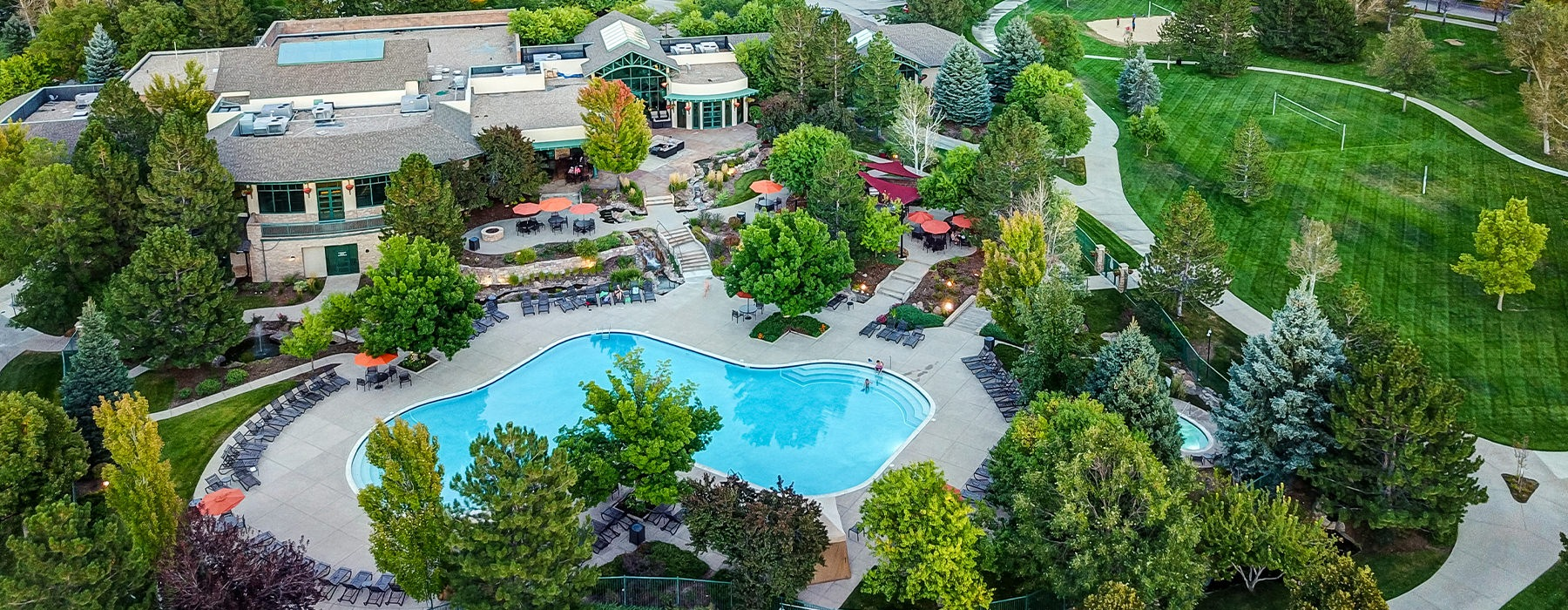 Large resort style sparkling blue swimming pool surrounded by a massive deck with plenty of seating.