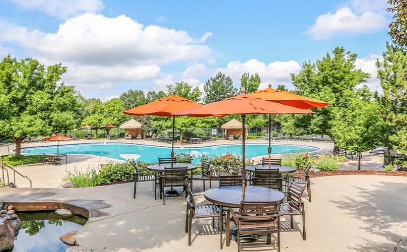 Swimming pool with multiple covered seating areas surrounded by trees and a fire pit.