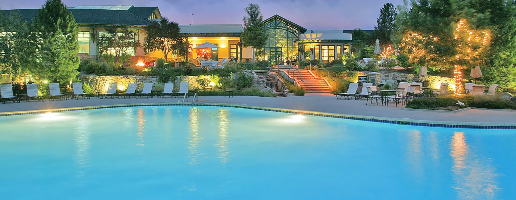 Large sparkling pool with the Palomino Park clubhouse in the back at night.