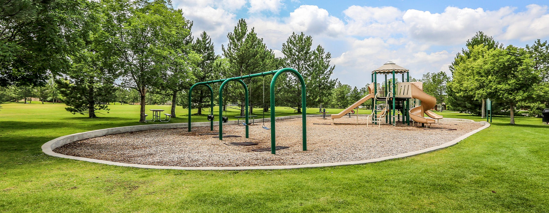 Large playground with swings and a play place surrounded by trees.